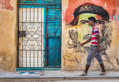 che guevara: Young cuban man walks by a colorful Che Guevara portrait painted on a shabby  old wall in Old Havana