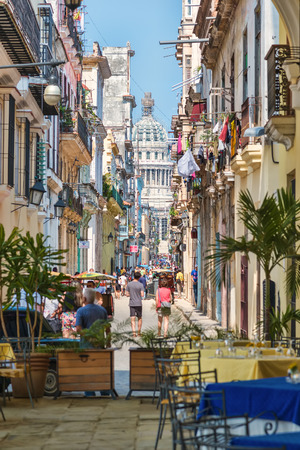 Tourists and cubans on a colorful street  in Old Havana