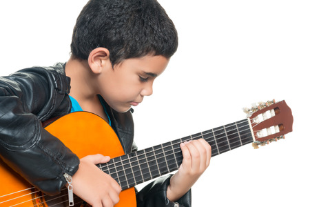 Cute hispanic boy playing an acoustic guitar isolated on a white background Imagens