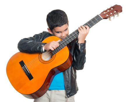 playing the guitar: Cute hispanic boy playing an acoustic guitar isolated on a white background Stock Photo