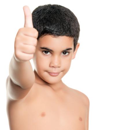 niño sin camisa: Muchacho hispánico Sin camisa haciendo un pulgar hacia arriba signo aislado en blanco Foto de archivo