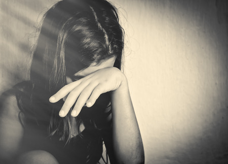 domestic: Monochrome portrait of a sad and lonely girl crying with a hand covering her face (with space for text) Stock Photo