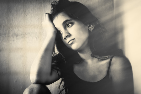 abused: Monochrome portrait of a sad girl sitting in a corner with a dirty wall background