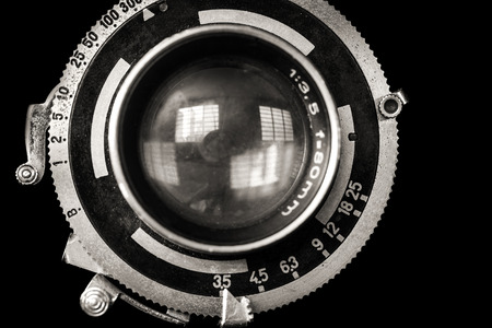 Vintage camera lens closeup isolated on black