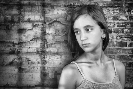 deprese: Smutný a osamělý dospívající dívka stojící vedle grunge cihlové zdi