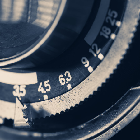 and aperture: Close-up detail of a vintage camera lens and aperture selection lever