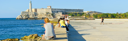 seawall: People at the Malecon seawall in Havana with a view of El Morro castle Editorial