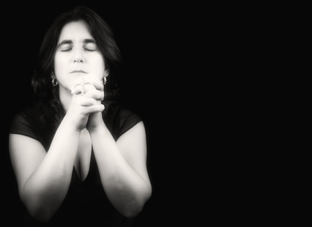 meditation woman: Hispanic woman praying with her eyes closed and holding a small crucifix isolated on black