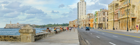 seawall: The Malecon seawall in Havana with a view of old buildings people and old cars Editorial