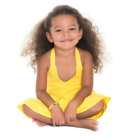 Mooie kleine Afrikaans-Amerikaanse of Spaanse meisje zittend op de vloer geïsoleerd op wit