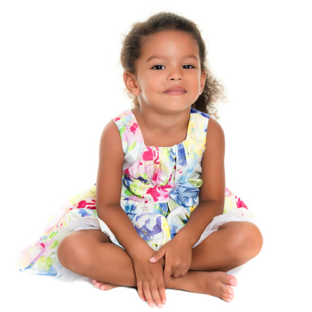 afro caribbean ethnicity: Beautiful small african-american or hispanic girl sitting on the floor isolated on white