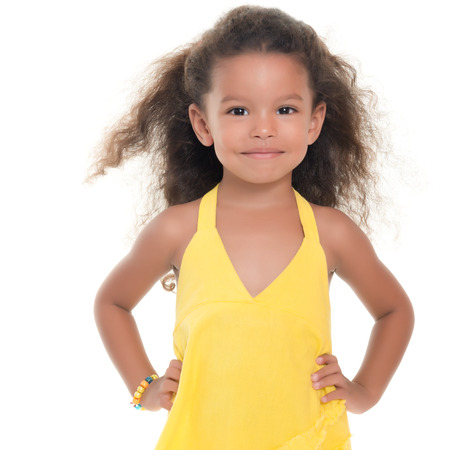 afro caribbean: Cute small african-american or hispanic girl wearing a yellow summer dress isolated on white Stock Photo