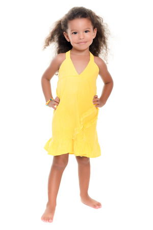 afro caribbean ethnicity: Cute small african-american or hispanic girl wearing a yellow summer dress isolated on white Stock Photo