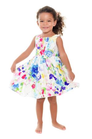 bebes niñas: Hermosa niña afroamericana o hispana con un vestido de flores de verano aislado en blanco Foto de archivo
