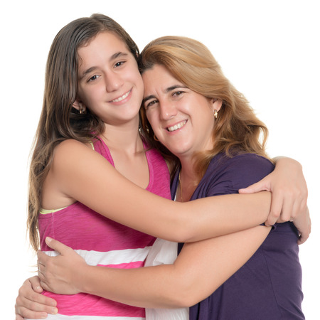 Hispanic teenage girl hugging her mother isolated on a white background Фото со стока