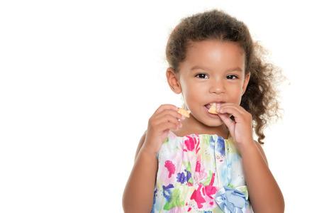 Pequeña muchacha linda que come una galleta aislado en blanco Foto de archivo
