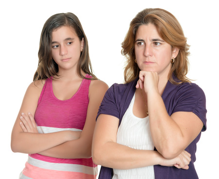Mother and her teenage daughter sad and angry at each other isolated on white Stock Photo