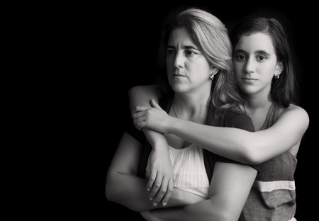 Emotional black and white portrait of a sad and angry mother with her teen daughter embracing her