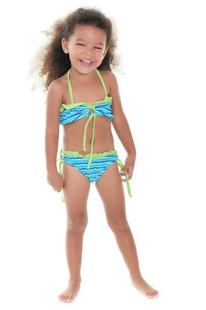 children swimsuit: Cute small african-american or hispanic girl wearing a bikini isolated on white