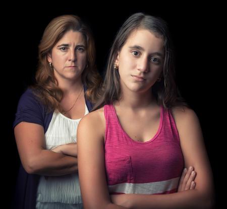jeune fille adolescente: Adolescente et sa mère triste et en colère les uns les autres isolé sur noir