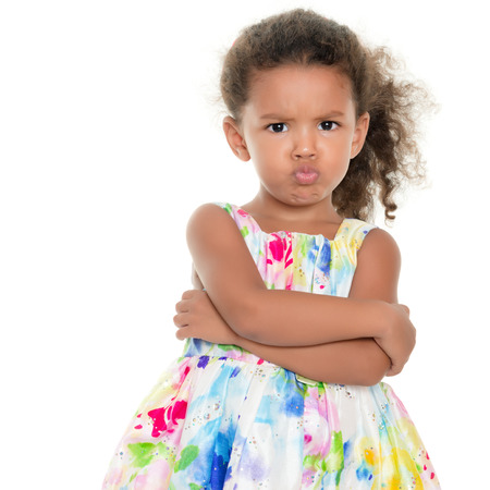 Cute small girl making a funny angry face isolated on white Foto de archivo