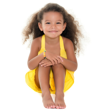 afro caribbean ethnicity: Cute small african-american or hispanic girl sitting on the floor isolated on white Stock Photo