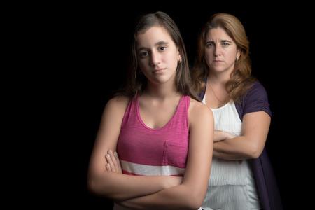 madre e hija: Adolescente y su madre triste y enojado el uno al otro aislado en negro