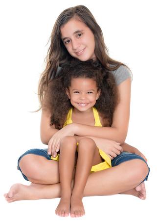 白の分離されたアフリカ系アメリカ人少女を抱き締めるヒスパニック系 10 代 写真素材