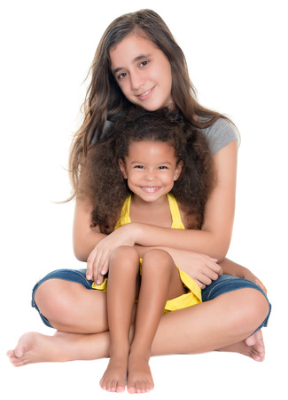 Hispanic teen hugging a little african-american girl isolated on white Фото со стока - 42299632