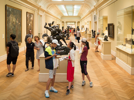 rodin: Visitors admiring sculptures by Auguste Rodin and paintings at the Metropolitan Museum of Art in New York