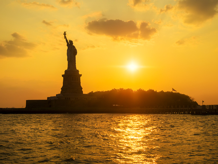 La estatua de la libertad en la puesta del sol con reflexiones sobre el océano