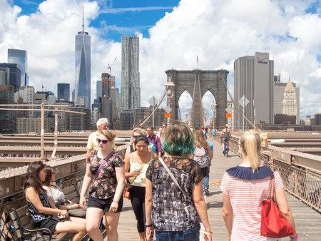 personas en la calle: Los locales y los turistas que cruzan el puente de Brooklyn en Nueva York
