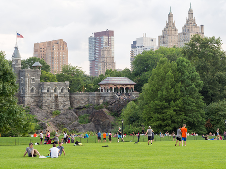 united states: People enjoying a day at Central Park with a view of Belvedere Castle and nearby historic buildings in New York