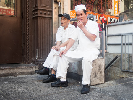 enclave: Old chinese inmigrants working a cooks at Chinatown in New York Editorial