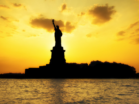 new york silhouette: Silhouette of the Statue of Liberty at sunset with reflections on the ocean