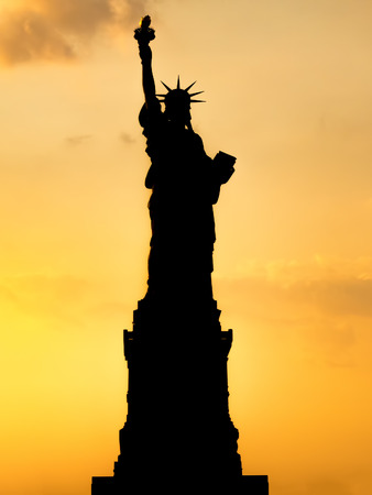 statue: Silhouette of the Statue of Liberty at sunset