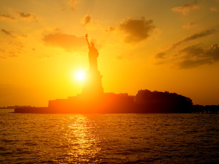 statue: The Statue of Liberty at sunset with the sun shining on the ocean Stock Photo