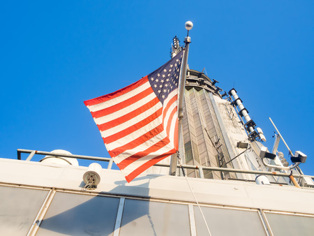 empire state building: American flag on top of the Empire State Building in New York City Editorial