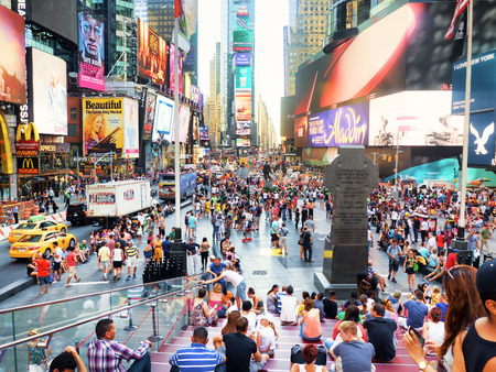 Tourists and colorful neon billboards at Times Square in New York City