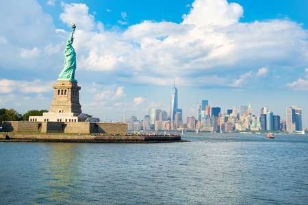The Statue of Liberty with the downtown Manhattan skyline on a beautiful summer day