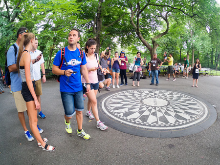 commemorating: Tourists at the Imagine mosaic commemorating John Lennon at Strawberry Fields in Central Park at New York City Editorial
