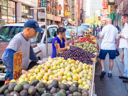 Chinese immigrants selling exotic fruits at Chinatown in New York City