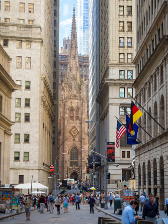 Wall Street on Manhattan Financial District with Trinity Church on the background