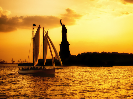 sailboat: Silhouette of the Statue of Liberty and a sailboat during a beautiful sunset