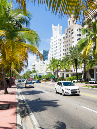 Street scene with traffic and  famous hotels at Collins Avenue in Miami Beach