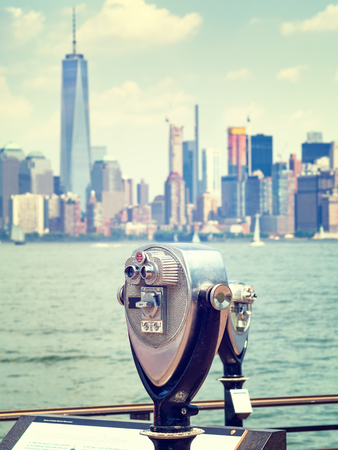 see the usa: Vintage toned binoculars looking at the downtown Manhattan skyline from Liberty Island