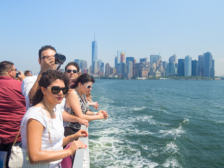 ny: Tourists in a cruise ship on the bay of New York with the Manhattan skyline on the background
