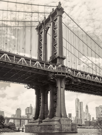 Black and white view of the Manhattan bridge in New York with the city skyline on the background
