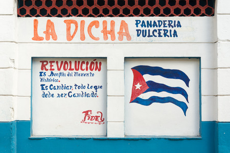 castro: Revolutionary slogan and cuban flag painted on a wall in Havana