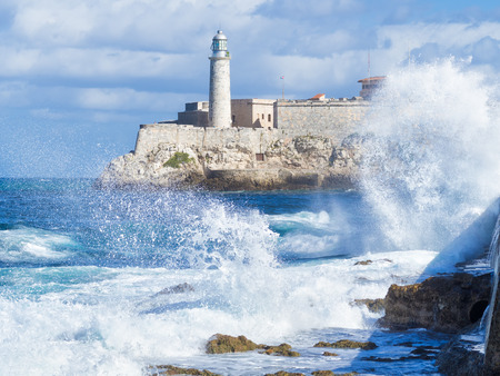 seawall: The Morro Castle in Havana with a stormy ocean and big waves crashing on the seawall